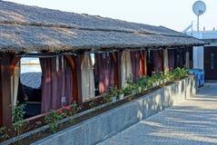 一部分的一个长的棕色大阳台在有帷幕和花盆的一个茅屋顶下与花 库存图片