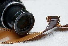 一部分的一台黑照相机和在灰色背景的一部棕色影片 图库摄影