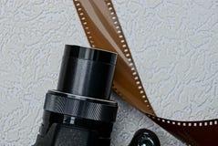一部分的一台黑照相机和在灰色背景的一部棕色影片 库存图片