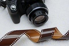 一部分的一台黑照相机和在灰色背景的一部棕色影片 免版税库存照片