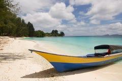 一部分的一条小船在王侯ampat a的一个热带海滩停泊了 免版税库存图片