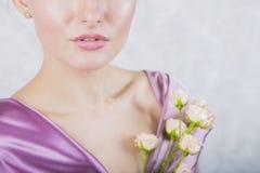 一部分的与乳脂状的玫瑰花束的美丽的女孩` s面孔 免版税库存照片