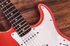 一部分的与光滑的结束、提取和控制旋钮的现代电六串吉他红颜色在木背景分类 免版税图库摄影