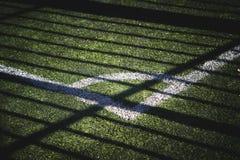 一部分的与标号的橄榄球场和从太阳的一片树荫 免版税库存图片