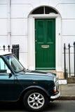 一部分的与绿色门和停放的汽车的一个大厦门面, 免版税库存照片
