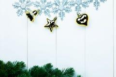 一部分的云杉的圣诞树和金黄装饰品和雪花在白色木背景 免版税库存照片