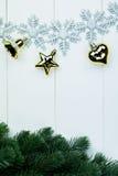 一部分的云杉的圣诞树和金黄装饰品和雪花在白色木背景 库存图片
