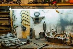 一部分的在一张桌上的摩托车引擎在车间 库存图片