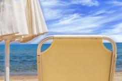 一部分的在海滩的sunbed和遮光罩伞 库存图片