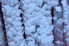 一部分的在白色雪下的问题在街道上 库存图片