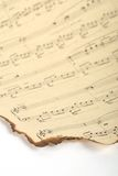 一部分的在葡萄酒纸和白色背景的老被烧的音乐纸张 库存图片