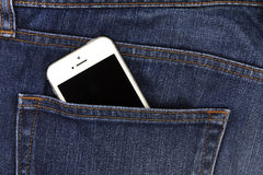 一部分的在蓝色牛仔布的后面口袋的流动白色手机 库存图片