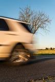 一部分的在行动的白色汽车 有一棵树的一条涂柏油的农村路在路旁 免版税库存图片