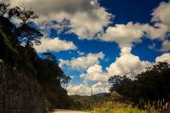 一部分的在被遮蔽的岩石小山多云蓝天的柏油路 免版税图库摄影