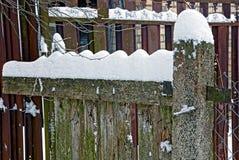 一部分的在雪下的木灰色篱芭 库存图片