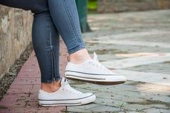 一部分的少女的腿 牛仔裤和运动鞋 免版税图库摄影