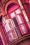 一部分的房子的墙壁 对阳台的门 明亮的颜色 深桃红色和黄绿 库存图片