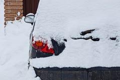 一部分的有一个车灯的一辆蓝色汽车在白色雪下 免版税库存照片
