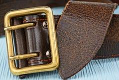一部分的有一个铜扣的一条棕色传送带在一张蓝色桌上 免版税库存图片