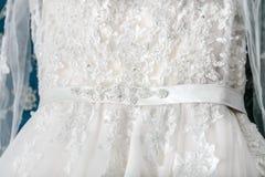 一部分的有光亮的假钻石的白色豪华新娘礼服 新娘 婚礼围腰 特写镜头 库存照片