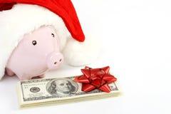 一部分的有圣诞老人帽子的存钱罐和堆金钱美国人与红色弓的一百元钞票 免版税库存照片