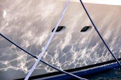 一部分的有在港口停住的蓝色绳索的白色游艇 免版税库存照片