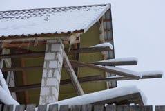 一部分的有板条和瓦片的一个未完成的顶楼房子在白雪下 免版税库存照片