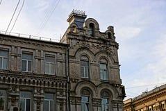 一部分的有窗口和一个屋顶的一个老砖房子反对天空 库存图片