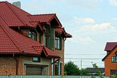 一部分的有红色铺磁砖的屋顶的一个砖砖房子 免版税图库摄影