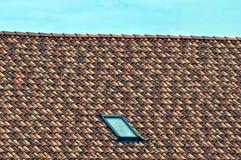 一部分的有色的铺磁砖的表面和一个小窗口的屋顶在天空背景 库存图片