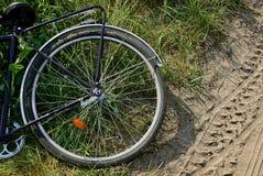 一部分的有轮子的一辆自行车在草说谎在路附近 免版税库存照片