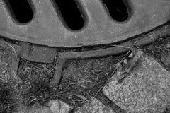 一部分的有铺路石的下水道舱口盖 免版税库存照片