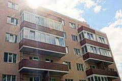 一部分的有阳台和窗口的一个棕色房子反对天空在阳光下 免版税库存图片