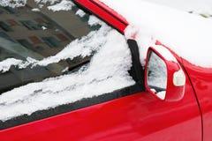 一部分的有雪特写镜头的前面镜子的红色汽车, 库存照片