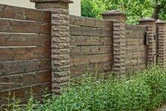 一部分的木板和砖棕色篱芭在绿草 库存照片