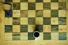一部分的棋老木桌和咖啡杯 图库摄影