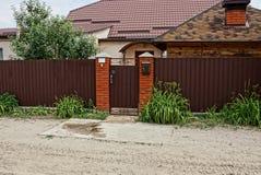 一部分的棕色金属篱芭和在街道上的一个门在路附近的草 免版税库存图片