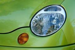 一部分的汽车:前灯和转弯信号在绿色汽车 库存图片