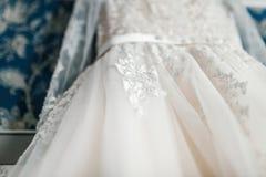 一部分的特写镜头图象的在蓝色墙壁的背景的白色豪华新娘礼服 底视图 库存图片