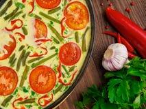 一部分的生铁平底锅用炒蛋、蕃茄和othe 库存图片