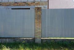 一部分的砖和金属外部灰色篱芭  库存图片