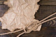 一部分的老被烧的羊皮纸和大麻绳索说谎在与黄柏的桌上的结完成 您的标签的框架 库存照片
