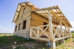 一部分的自然木材材料未完成的木生态传统村庄与陡峭的屋顶框架和附加的大阳台的 免版税库存照片