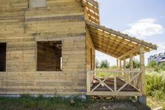 一部分的自然木材材料未完成的木生态传统村庄与陡峭的屋顶框架和附加的大阳台wi的 库存图片