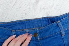 一部分的蓝色牛仔布裙子和女性手 详细资料 库存照片