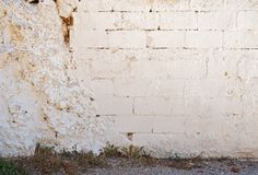 一部分的被放弃的白色砖破裂的灰泥墙壁 库存图片