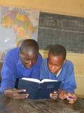 读一部圣经的孩子在教室 库存照片
