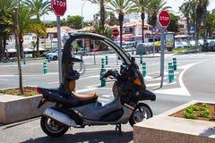 一部银色被盖的小型摩托车在街道上停放了在Playa美洲日报在Teneriffe加那利群岛  库存图片