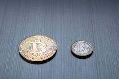 一金黄bitcoin和一枚欧洲硬币在金属背景 C 库存照片