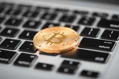 一金黄bitcoin当在膝上型计算机键盘安置的世界主要cryptocurrency 库存图片